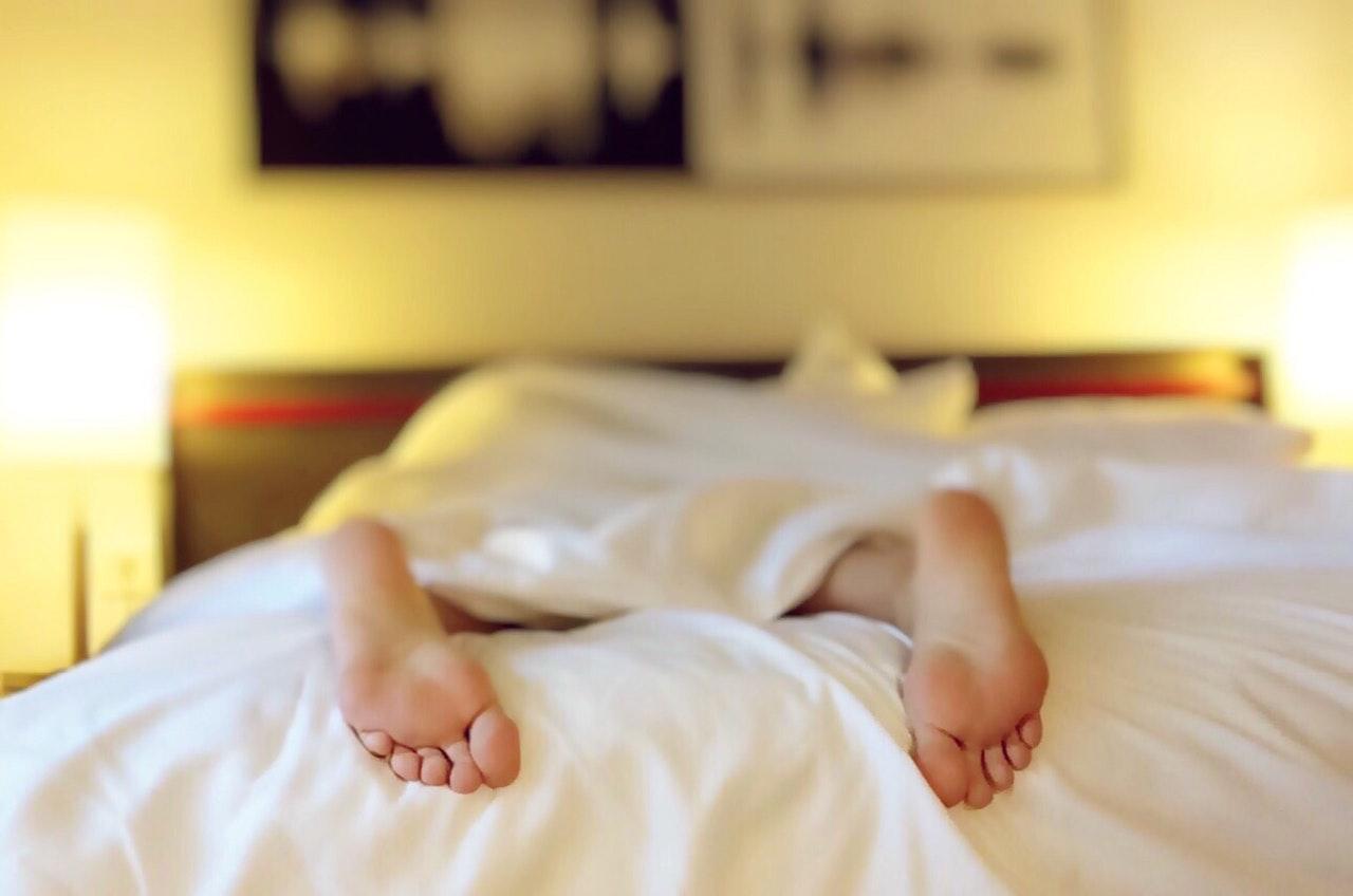 Person sover i seng med fødderne ude